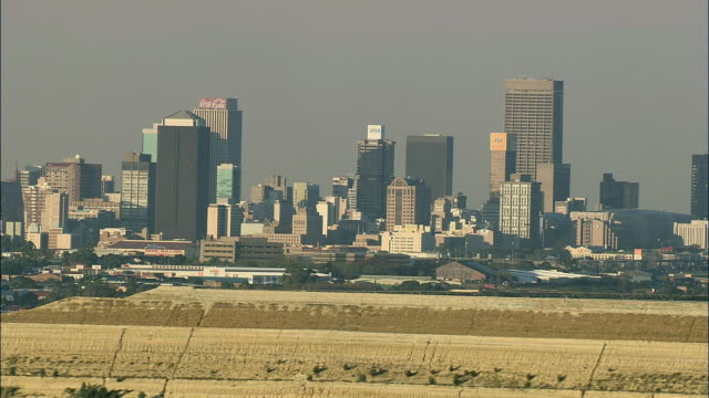 vídeos de stock, filmes e b-roll de aerial ws downtown skyline with mine waste in foreground, johannesburg, gauteng, south africa - 2007