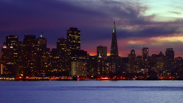 T/L Downtown skyline with ships passing at dusk / San Francisco