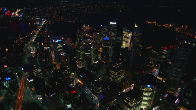 AERIAL ZI Downtown skyscrapers and Sydney Harbor at night / Sydney, Australia
