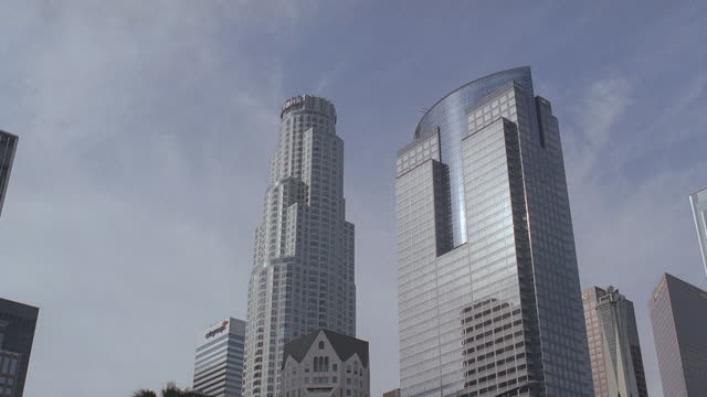 la downtown skyscrapers looming over smaller buildings / los angeles, california, united states - us bank tower stock videos & royalty-free footage