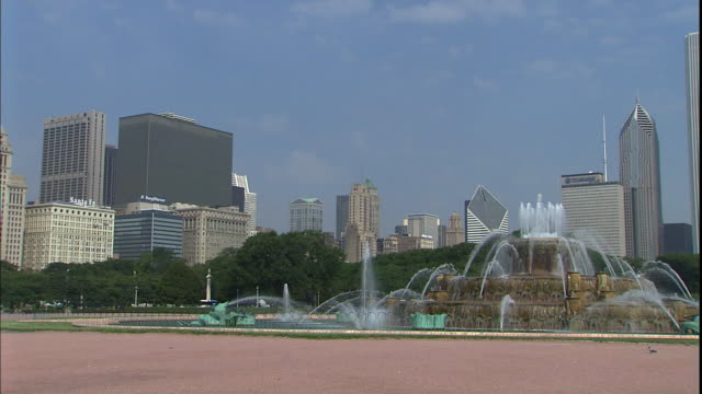 downtown skyscrapers rise behind chicago's majestic buckingham fountain. - buckingham fountain stock videos & royalty-free footage