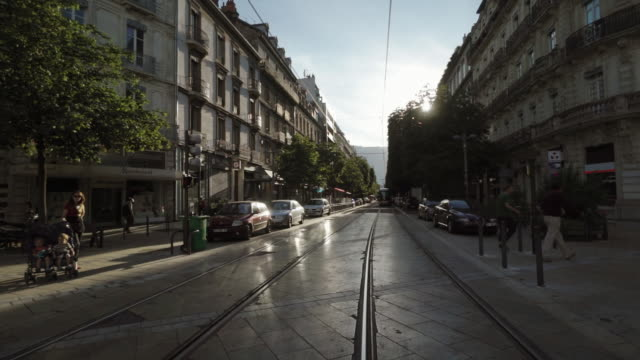 downtown street with mero rail on sunny day - grenoble, france - ヨーロッパ点の映像素材/bロール