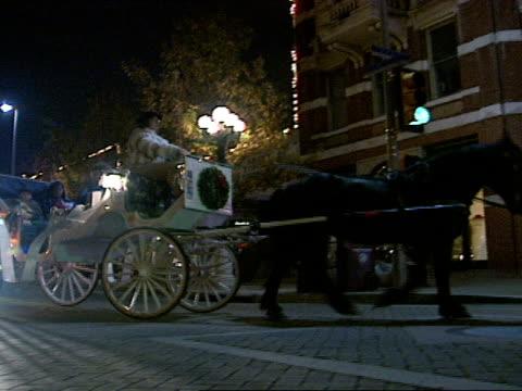 vídeos y material grabado en eventos de stock de downtown streets w/ white carriage, drawn by dark horse, waiting at intersection. horse & carriage passing. dolly behind carriage on two lane... - tracción de caballos
