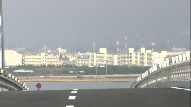 downtown tokyo looms on the horizon beyond the tokyo gate bridge. - kantilever bildbanksvideor och videomaterial från bakom kulisserna