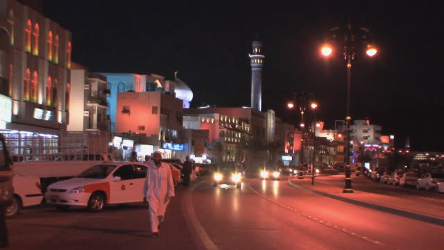 ws downtown traffic and arab man walking past camera, muscat, oman - dischdascha stock-videos und b-roll-filmmaterial