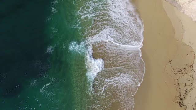 Downward Aerial Low: 4K UHD Aqua waves crashing on beach