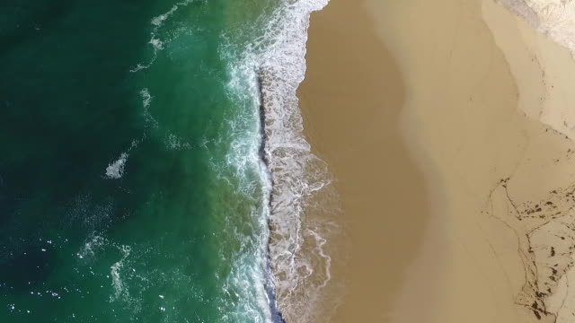 Downward Aerial Low: Aqua waves crashing on beach