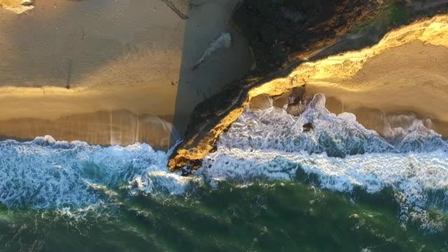 downward aerial medium: pelican formation flies past coastal beach - pelican stock videos & royalty-free footage