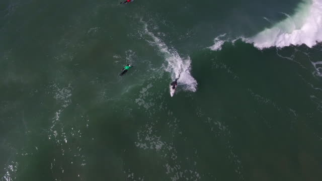 downward aerial track: surfer cutbacks 4k uhd - santa cruz california stock videos and b-roll footage