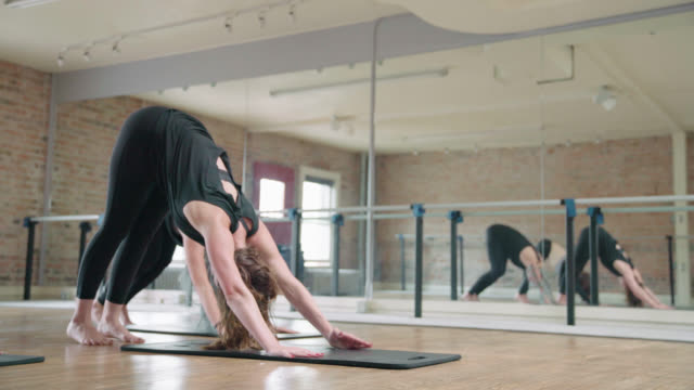 downward dog in fitness class - barre stock videos & royalty-free footage