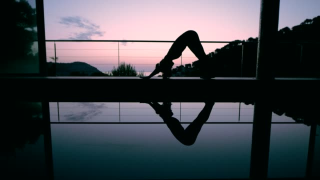 downward facing dog pose. woman doing yoga by the pool - posture stock videos & royalty-free footage