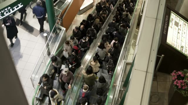 vídeos de stock e filmes b-roll de downward pan of crowded up and down escalator - cheio