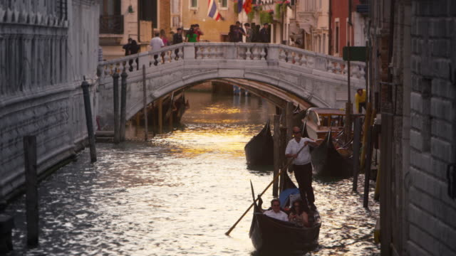 Downward slow motion tilt shot of focusing on a gondolier in Venice, Italy.