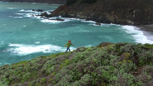 downward tilting aerial of woman hiking in big sur - coastline stock videos & royalty-free footage