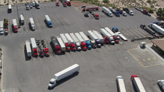 downward tilting drone shot of truck stop - articulated lorry stock videos & royalty-free footage