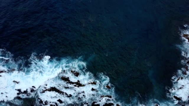 Downward View of Waves Crashing Over Rocky Shoreline