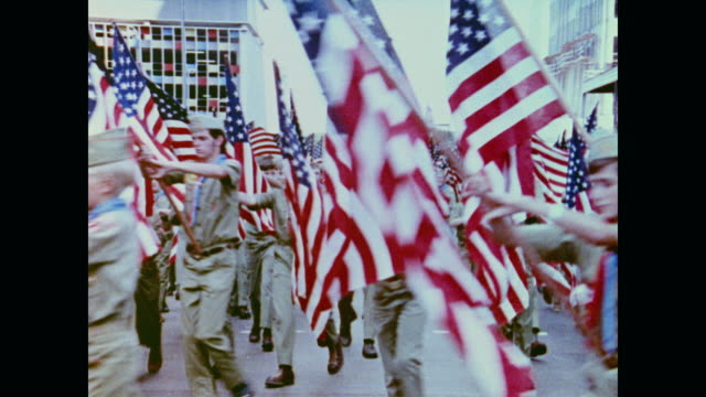 dozens of boy scouts carry large american flags in the apollo homecoming parade - boy scout stock videos & royalty-free footage