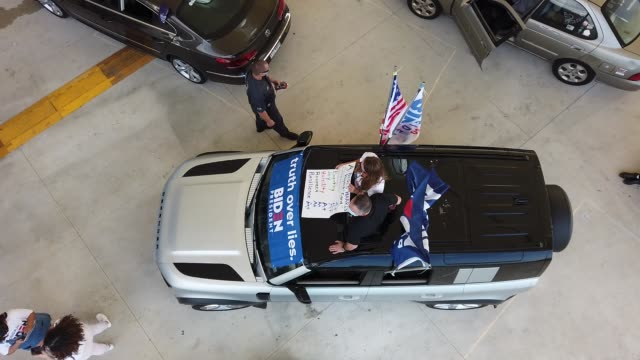 stockvideo's en b-roll-footage met dozens of cars park under a shaded pavilion as democratic presidential nominee joe biden delivers remarks during a drive-in voter mobilization event... - pembroke