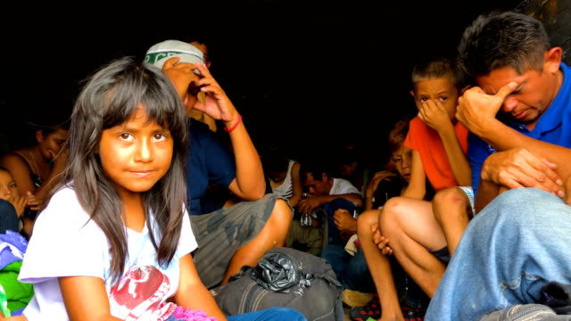 Dozens of children and adults squeeze into the back of a container truck headed to an unknown location as members of the Central American migrant...