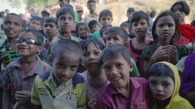 Dozens of children crowd around in Kutupalong refugee camp in Bangladesh looking at the camera and the camera moves upwards Children make up over 50%...
