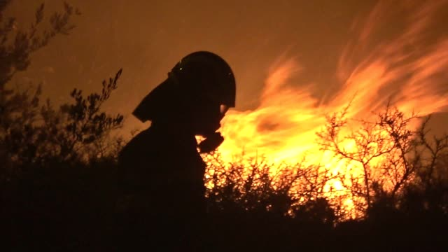 vídeos de stock e filmes b-roll de dozens of firefighters assisted by five waterdropping helicopters battled overnight a large brush fire south of athens in a forested area of kalyvia... - athens greece