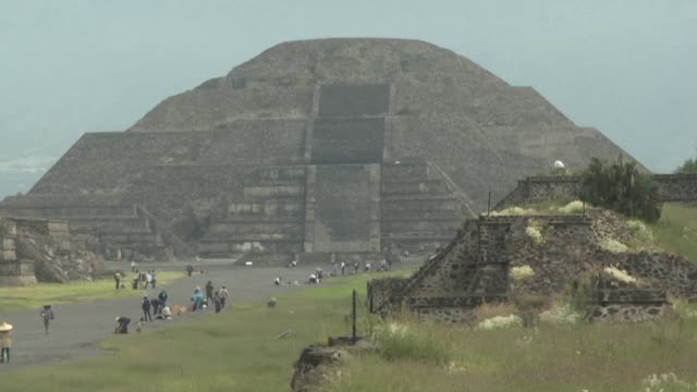 dozens of local and foreign tourists take selfies and stroll along the avenue that stretches between the majestic pyramids of teotihuacan mexico's... - mayan stock videos & royalty-free footage