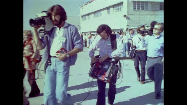 dozens of media people walk briskly across the runway carrying cameras, notepads, recorders and video recorders - 1977 stock videos & royalty-free footage