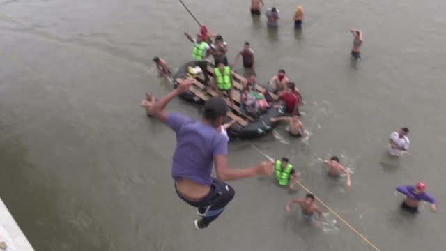 Dozens of migrants jump into the Suchiate River from the Guatemala Mexico border bridge to cross into Mexico using makeshift crafts after being...