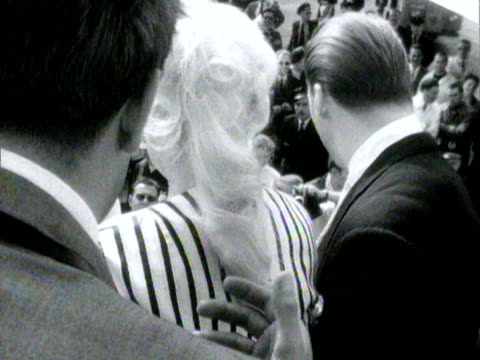 dozens of photographers greet jane mansfield and her husband as they arrive at nice airport - mickey hargitay stock videos & royalty-free footage