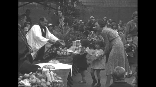 """dozens of school children carry harvest gifts, teachers usher them as parents look on / borough mayor makes speech """"thank you indeed for this... - basket stock videos & royalty-free footage"""