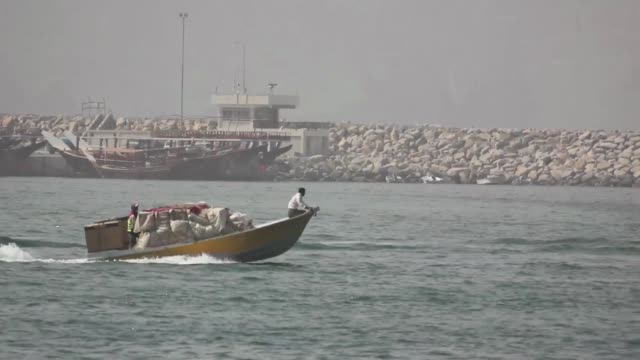 stockvideo's en b-roll-footage met dozens of unmarked speedboats pulled into oman's khasab port, breaking the dawn silence and marking the start of a wet and treacherous work-day for... - perzische golf