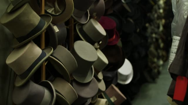 dozens of various hats hanging on poles in los angeles california on march 23rd 2015 shots interior wide shots on a wall of elegant top hats hanging... - table top shot stock videos and b-roll footage