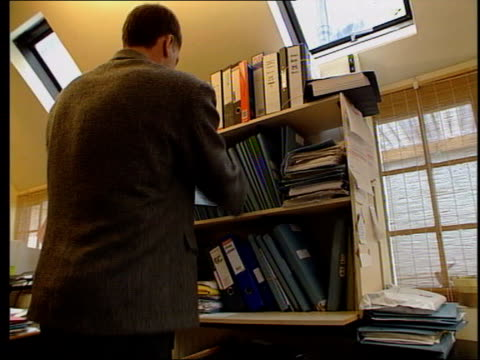 dr andrew wakefield sitting at desk reading notes - doctor who stock-videos und b-roll-filmmaterial