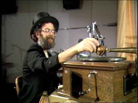 Dr Demento winds up his Victrola record player and plays records while ringing bells and playing toy instruments