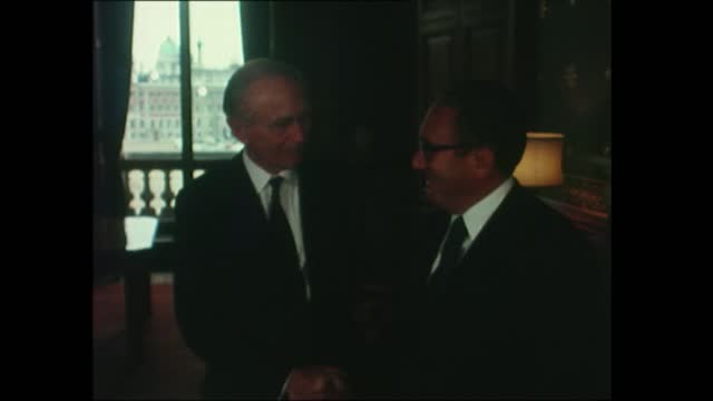dr henry kissinger arrives in uk; england, london: heathrow : ext dr henry kissinger down plane steps & greeted: pull out policeman with binoculars... - alec douglas home video stock e b–roll