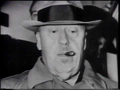 stockvideo's en b-roll-footage met dr. hugo eckener dressed in trench coat & hat w/ partially smoked cigar in mouth, looking down, face, eyes & nose. hearings: unidentified men sitting... - hoofddeksel