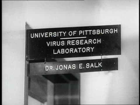 dr jonas salk talks to a coworker in the university of pittsburgh virus research laboratory - 発明家点の映像素材/bロール