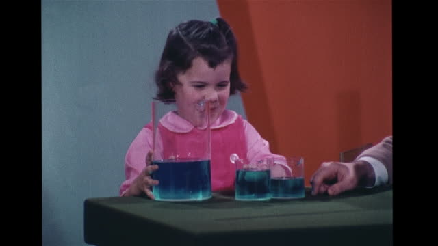 Dr Marshall Heath w/ preschool girl two glasses w/ same amount of water SOT pouring 'her' water into taller thinner glass which has more picks taller...