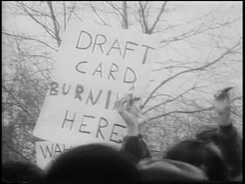 b/w 1967 draft card burning here sign above crowd at antiwar rally / central park nyc / newsreel - peace demonstration stock videos and b-roll footage