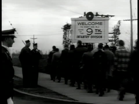 vídeos de stock, filmes e b-roll de draftees in civilian clothing walking into fort dix new jersey guards sign 'welcome 9th infantry division' . guards watching. draftees walking... - 1951