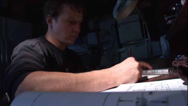 vídeos de stock, filmes e b-roll de a draftsman graphs information on paper. - papel quadriculado