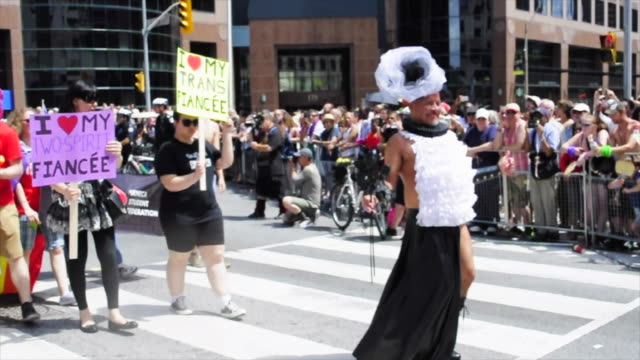 drag queen leading a block of people with signs reading 'i love my trans fiancee' the gay pride parade is a traditional celebration during the summer... - drag queen stock videos and b-roll footage