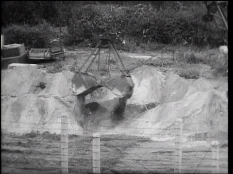 dragline dumping dirt during construction of ditch at berlin wall / east berlin - 1961 stock-videos und b-roll-filmmaterial