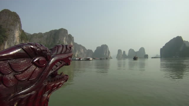 ws dragon bow of tourist boat with port on ha long bay in background / quang ninh , vietnam - bay of water stock videos & royalty-free footage