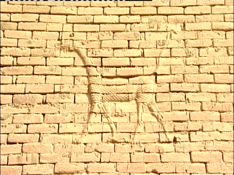 a dragon inlay decorates a brick wall in the ancient city of babylon. - babylon stock videos and b-roll footage