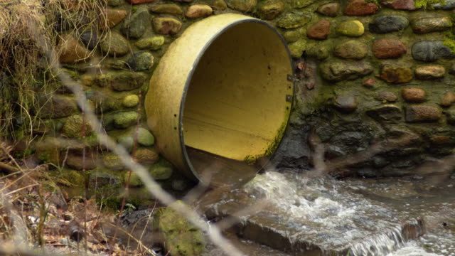 Drain system with water trickling out near autumn forest