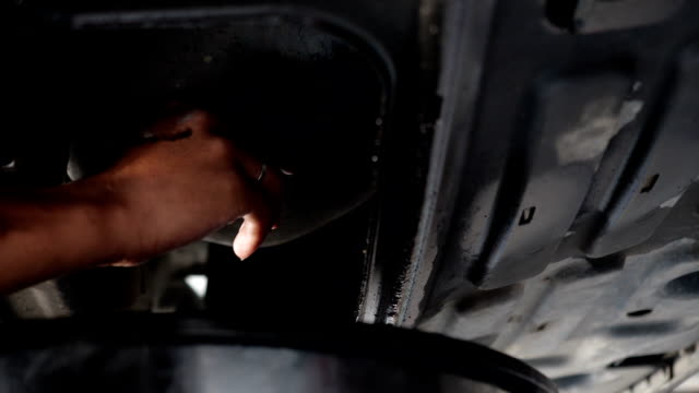 drain the old oil from the engine through the drain plug. - motor oil stock videos & royalty-free footage