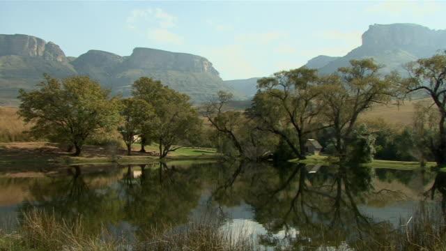 ws pan drakensberg mountain range reflected in lake / kwazulu-natal, south africa - drakensberg mountain range stock videos & royalty-free footage