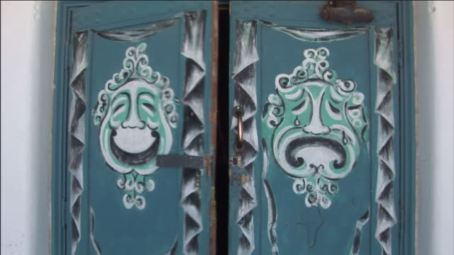 drama masks decorate the double doors of a small playhouse. - playhouse stock videos & royalty-free footage