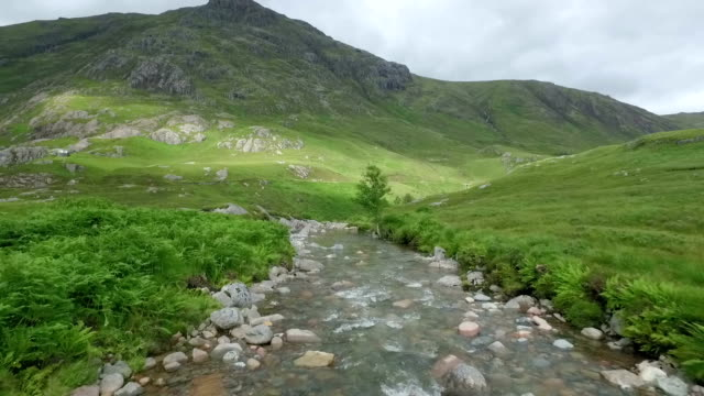 Dramatic aerial / drone shot in Glencoe along a river in the Scottish highlands